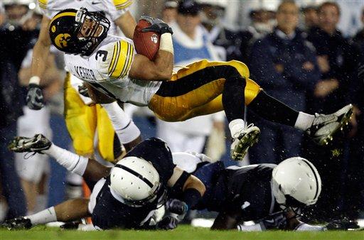 Iowa running back Brandon Wegher flips over Penn State defenders (picture courtesy AP Photo/Carolyn Kaster)